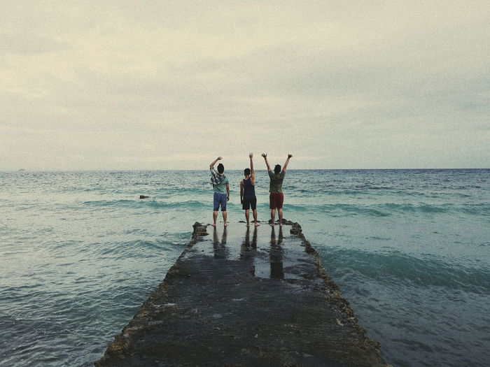 Rear View Of People Standing In Sea Against Sky