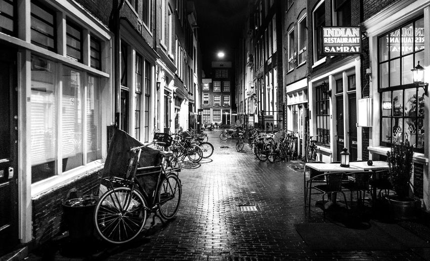Architecture Building Exterior Built Structure City Transportation Building Street Mode Of Transportation Land Vehicle Night Illuminated Bicycle No People Footpath Direction Outdoors Window The Way Forward Residential District Absence Alley