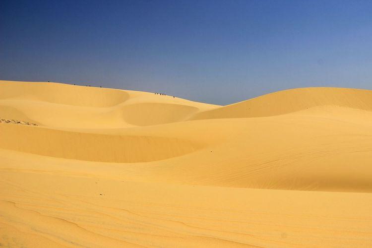 View of calm desert against clear blue sky