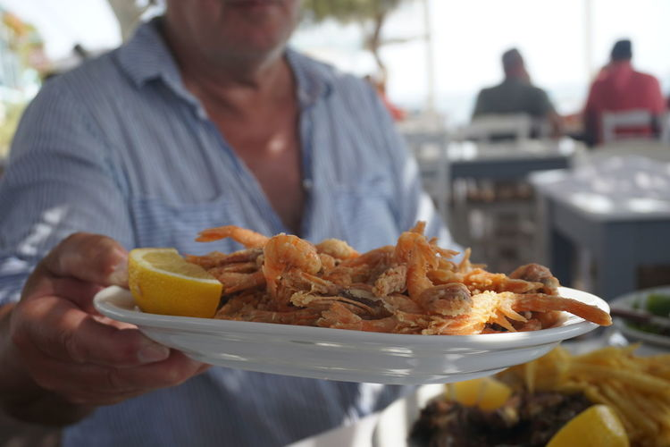 Midsection of man holding seafood in plate