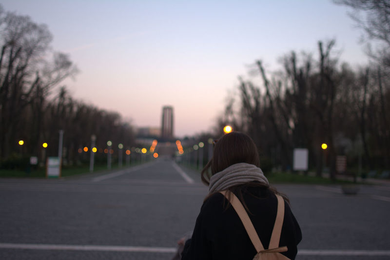 Rear view of woman in city against sky during sunset