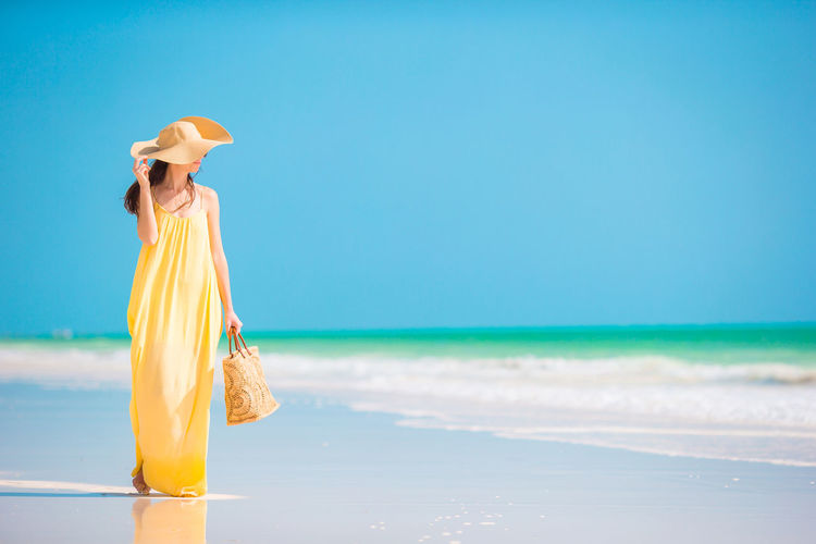 Woman with umbrella standing on beach against sky
