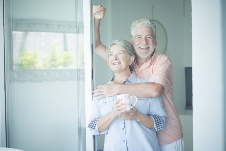 Smiling senior couple embracing at home