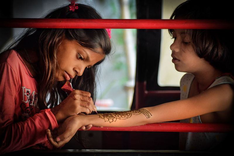 Girl applying henna tattoo on sister forearm