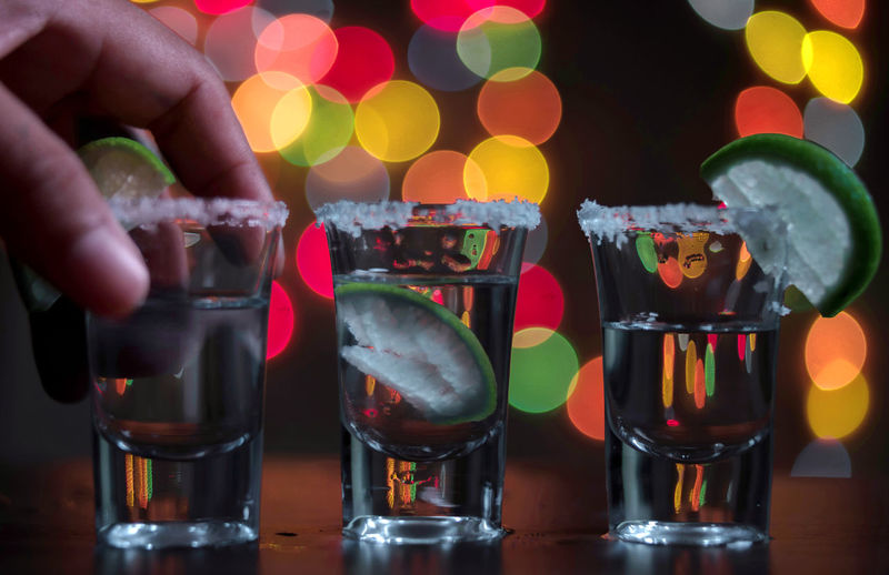 Cropped image of hand picking tequila shot at bar