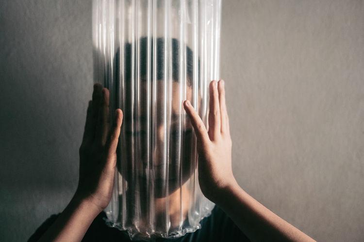 Boy wearing bubble wrap on face against wall