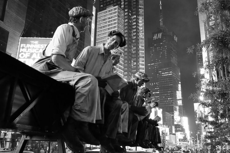 Low angle view of people sitting in city at night