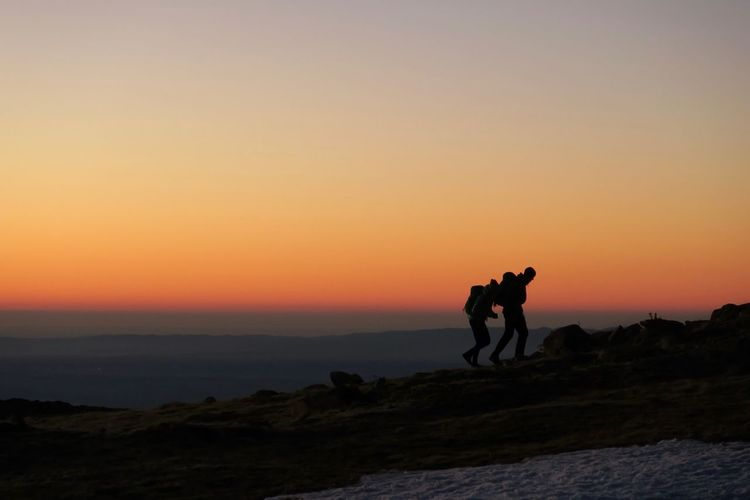 Silhouette friends walking on mountain against sky during sunset