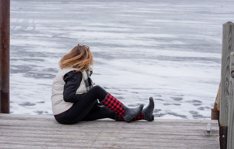 woman sitting on pier in winter looking at frozen lake Boots Frozen Lake Pier Beauty In Nature Blond Hair Buffalo Check Clothing Cold Temperature Day Dock Full Length Hair Hairstyle Leisure Activity Lifestyles Long Hair One Person Outdoors Real People Sitting Snow Warm Clothing Winter Women Wood - Material