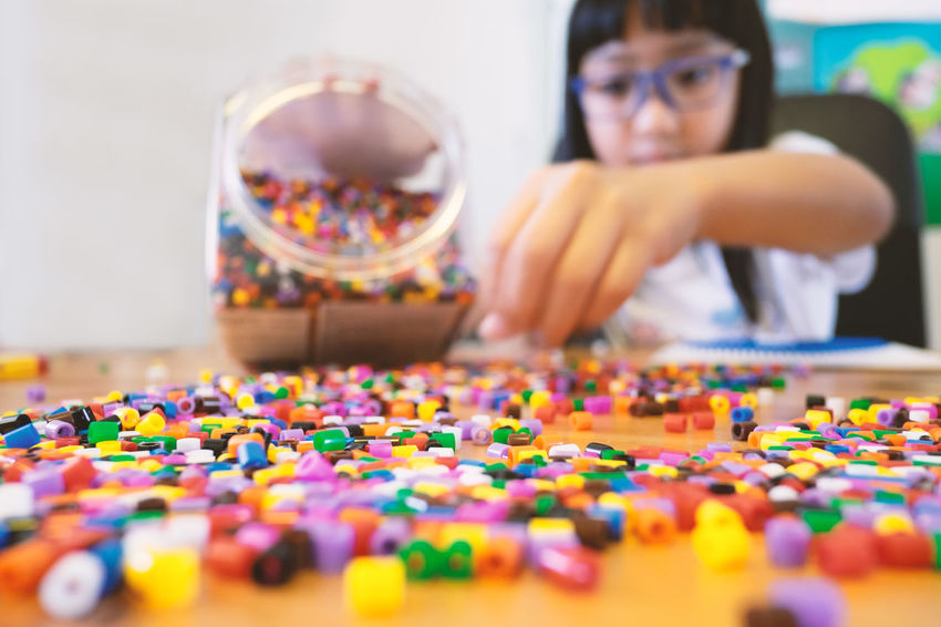 One Person Multi Colored Indoors  Front View Headshot Portrait Childhood Child Selective Focus Large Group Of Objects Glasses Eyeglasses  Looking Leisure Activity Girls Beads Toy Playtime Blocks Asian  Girl Kid Activity Home Education