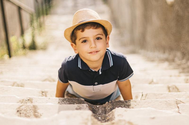 High angle portrait of cute boy wearing hat lying on steps