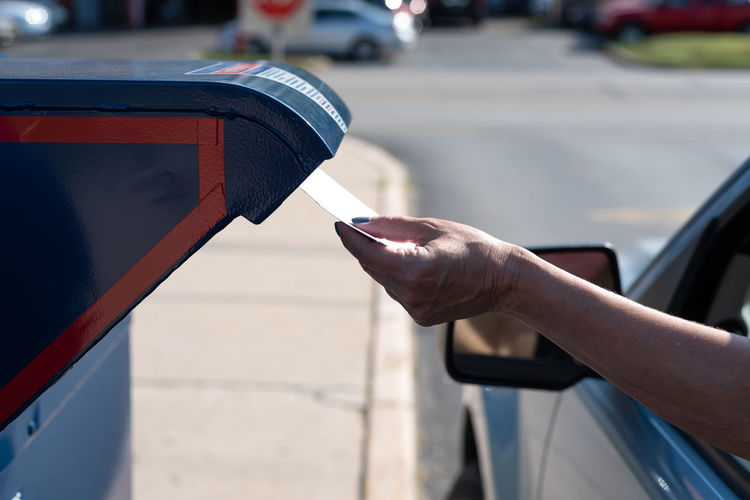 Cropped hand of woman inserting letter in mailbox through car window
