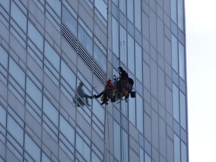 Low angle view of window washers on building