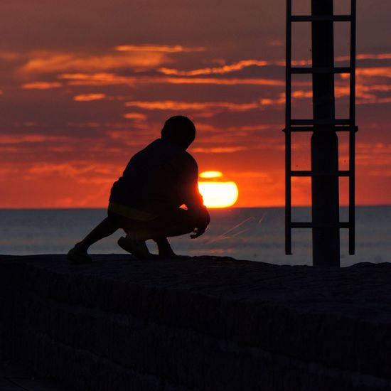 Silhouette Person Crouching On Retaining Wall Against Red Sky During Sunset