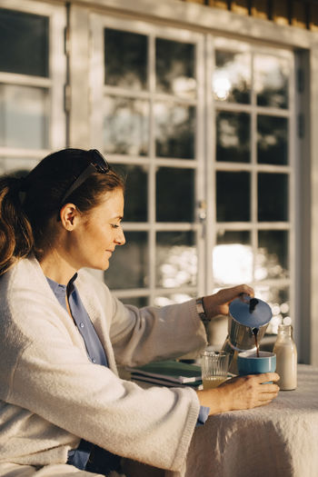 Side view of woman holding coffee cup on table