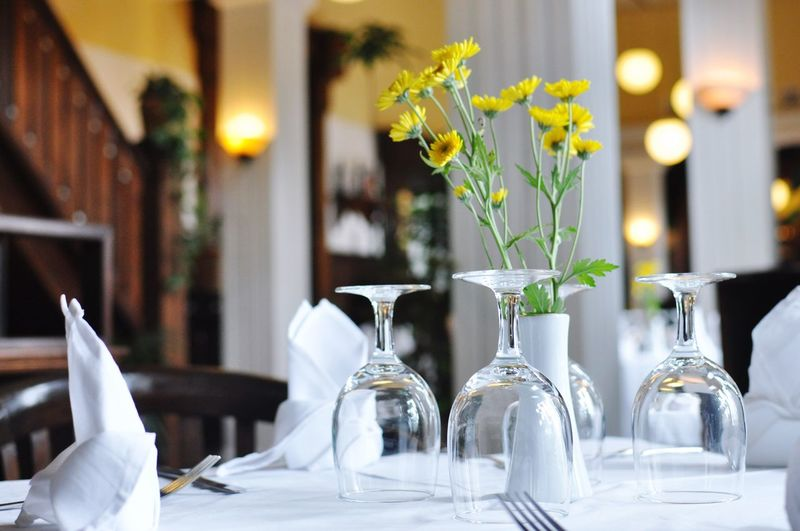 Close-Up Of Empty Wineglass By Flower Vase On Table At Restaurant