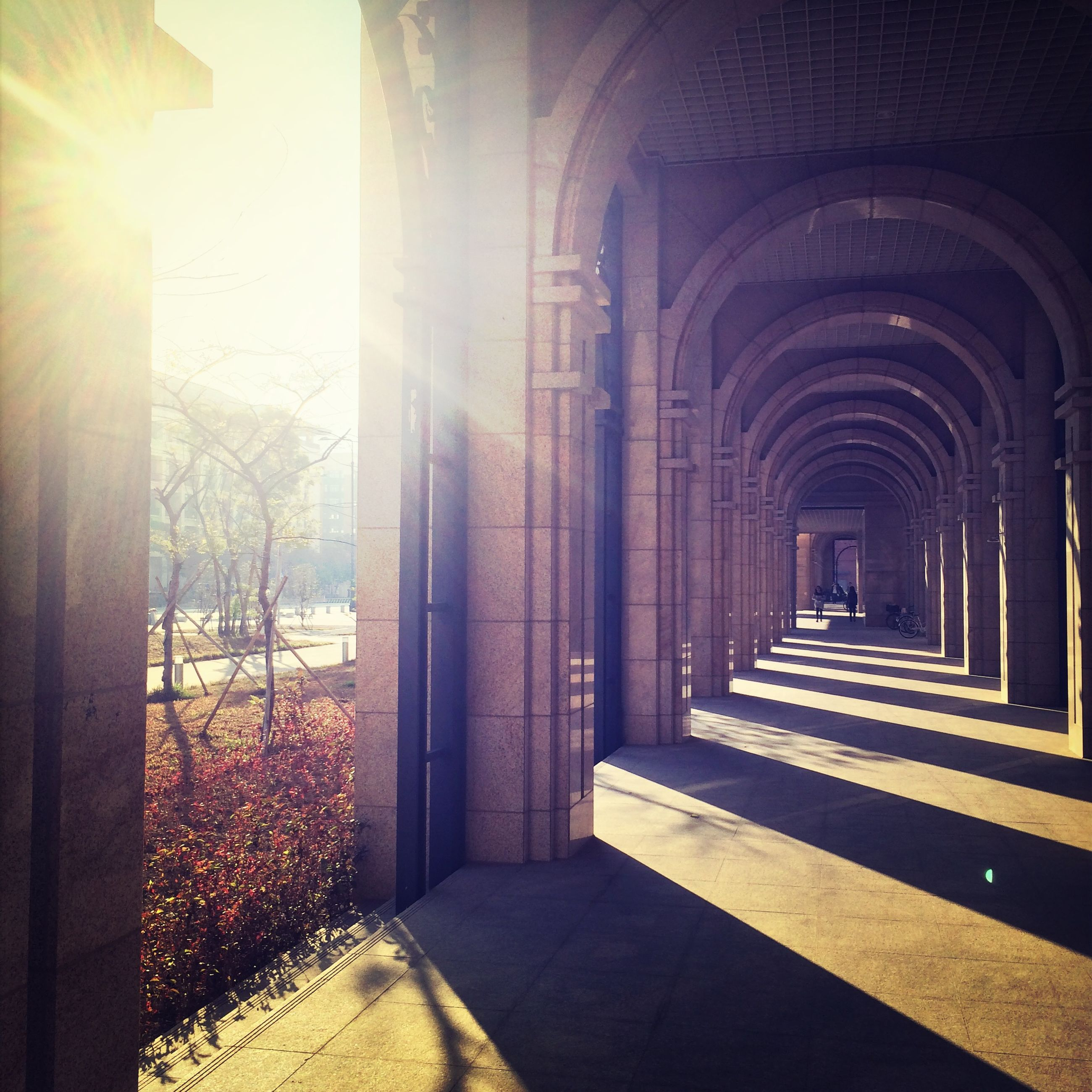 architecture, built structure, indoors, arch, architectural column, the way forward, corridor, sunlight, column, building exterior, in a row, colonnade, day, diminishing perspective, tiled floor, building, entrance, history, religion, shadow