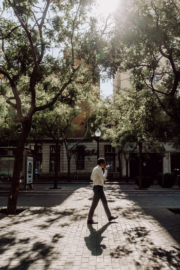 Barcelona The Street Photographer - 2018 EyeEm Awards Barcelona EyeEm Best Shots SPAIN Smoking Taking Photos City Eye4photography  Full Length Leisure Activity Lifestyles Light And Shadow Nature One Person Street Street Photography Streetphotography Sunlight Travel Destinations Tree Urban Waling Around Walking