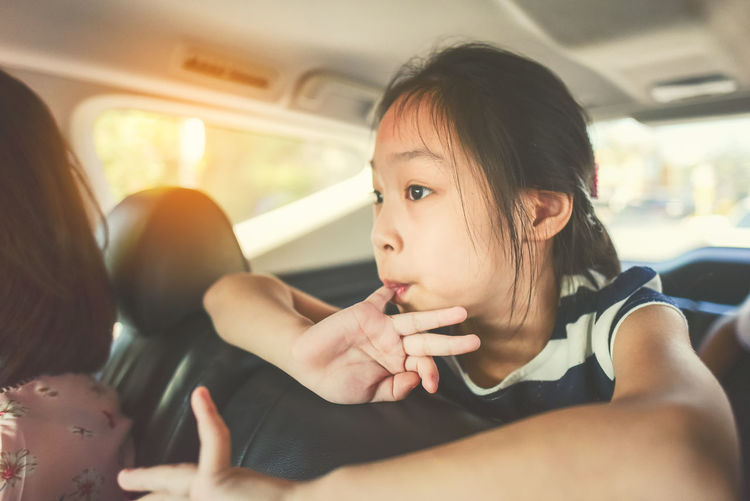 Girl with mother sitting in car