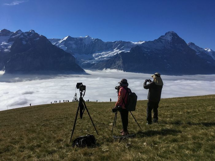 Man And Woman Photographing Snowcapped Mountains Amidst Cloudscape