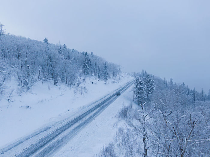 Snow covered road by trees against sky