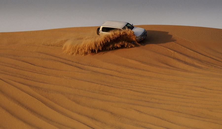 Off-road vehicle moving on sand at desert