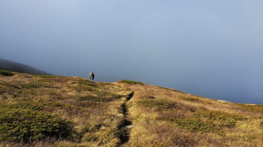 Man standing on landscape against foggy sky
