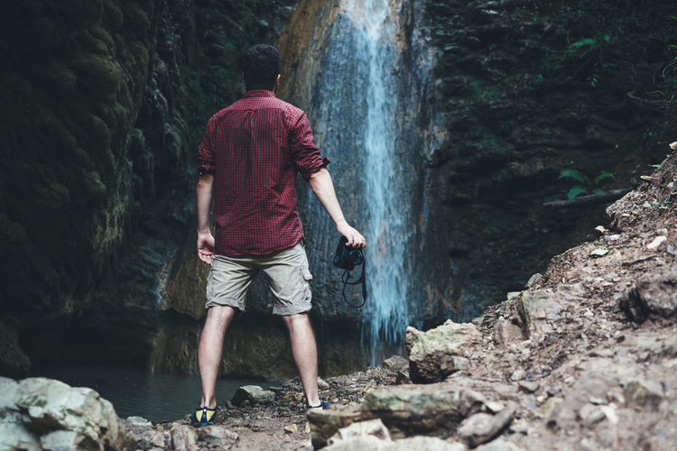 photographer into the nature Adventure Beauty In Nature Casual Clothing Flowing Flowing Water Forest Full Length Land Leisure Activity Lifestyles Men Motion Nature One Person Outdoors Photography Real People Rear View Rock Rock - Object Scenics - Nature Shorts Solid Standing Waterfall