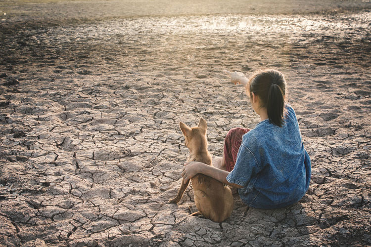 High Angle View Of Girl With Dog Sitting On Field During Drought