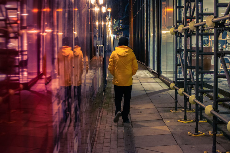 Rear View Illuminated Real People One Person Architecture Full Length Built Structure Night Building Exterior City Walking Lifestyles Street Direction Men Leisure Activity Footpath City Life Motion Scaffolding Scaffold