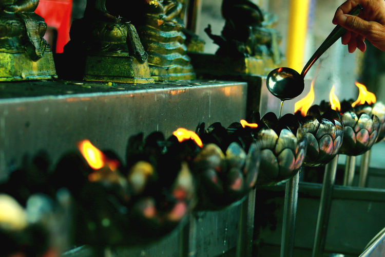 Cropped hand pouring oil in burning diyas at buddhist temple