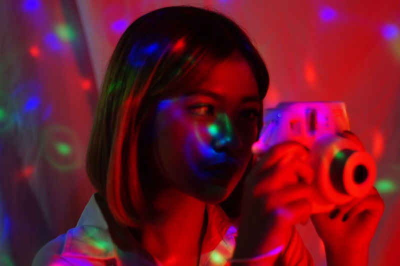 Portrait of young woman holding colorful light painting