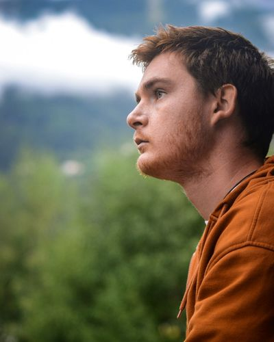 Profile view of thoughtful young man against trees