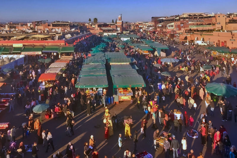 The Jemaa El-Fna Square at Marrakesh in Morocco. Buildings City City Life Crowd Day Downtown District Food Stalls High Angle View Jemaa El-Fna Square Large Group Of People Marrakesh Morocco Musicians Outdoors People Sky Snake Charmers Travel Destinations