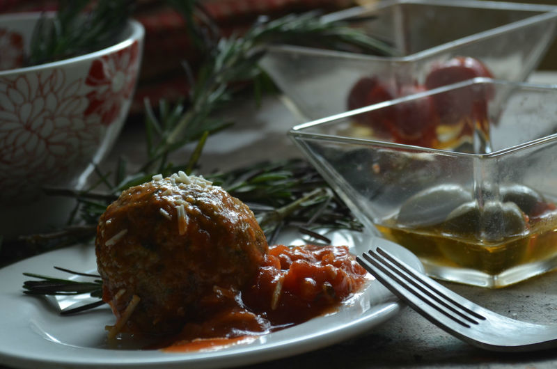 Meatballs and red sauce on plate, fork, green olives in glass dish
