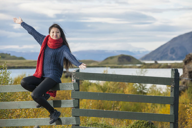 Woman standing by railing against mountain