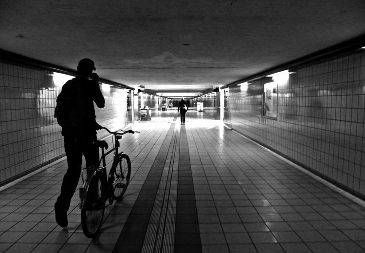Man With Bicycle Walking In Basement