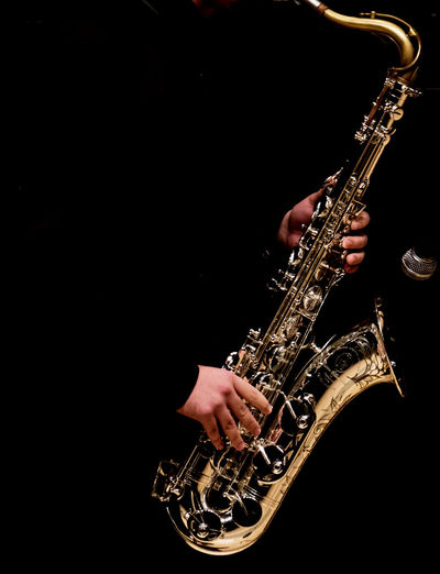 Man Playing Saxophone Against Black Background