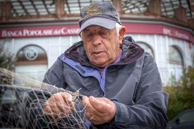 Il pescatore One Person Senior Adult Senior Men Males  Front View Real People Lifestyles Adult Men Day Portrait Waist Up Clothing Architecture Cap Holding Hat Focus On Foreground Outdoors Warm Clothing Fuji Xt20 Streetphotography Street Old-fashioned Pescatore