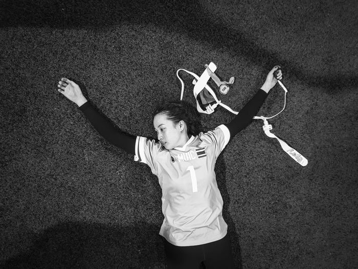 Directly above shot of female athlete lying on field