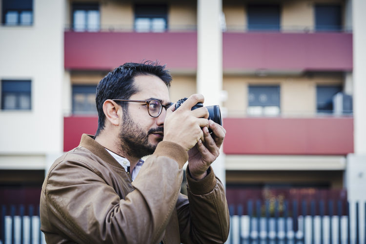 Side view of man photographing with camera against building