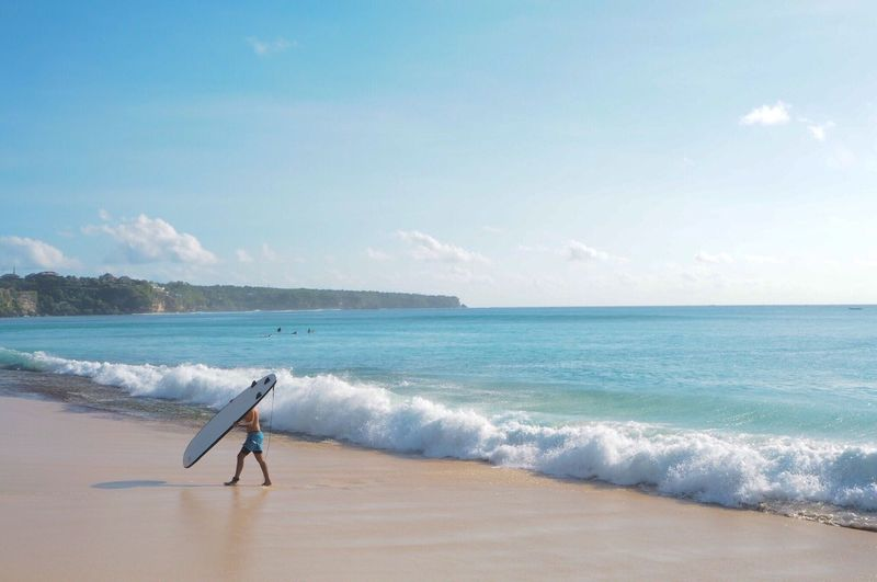 Sea Full Length Beach Water Wave Horizon Over Water Surfboard Sky Shore Surf Surfing Walking Side View Sport Motion Surfer Men Leisure Activity Water Sport Windsurfing Bali INDONESIA Travel Destinations Non-urban Scene Landscape