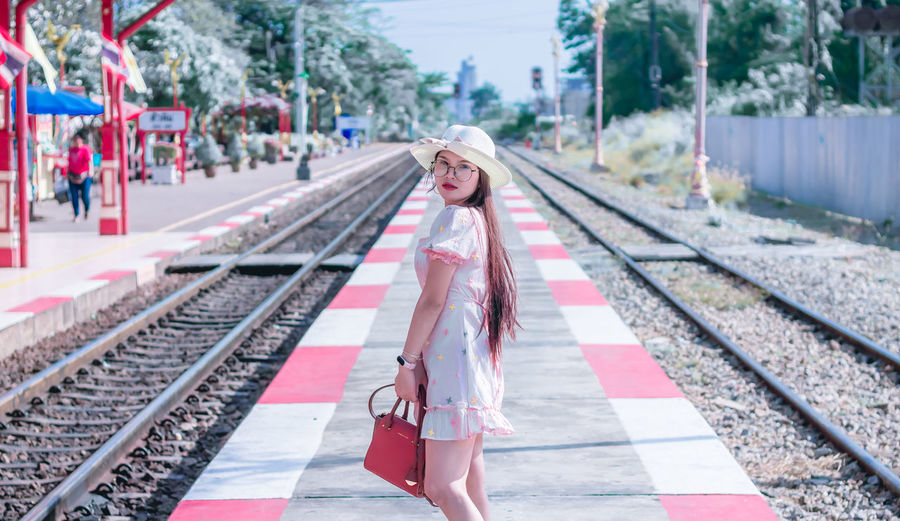 Portrait of smiling woman standing on railroad station platform