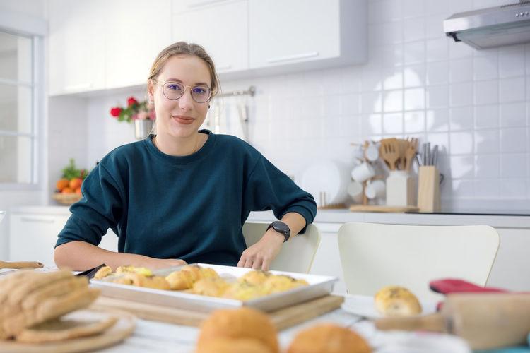 Portrait of woman having food on table