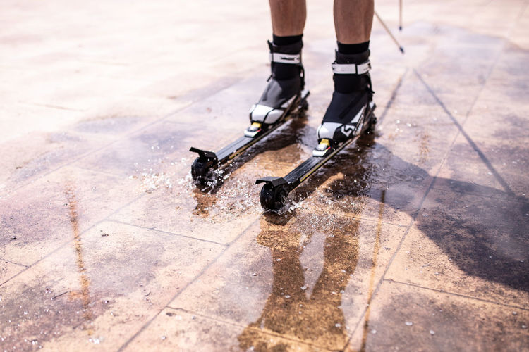 Low Section Of Person Inline Skating On Wet Tiled Floor