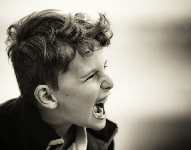 Close-Up Of Angry Boy Shouting Outdoors