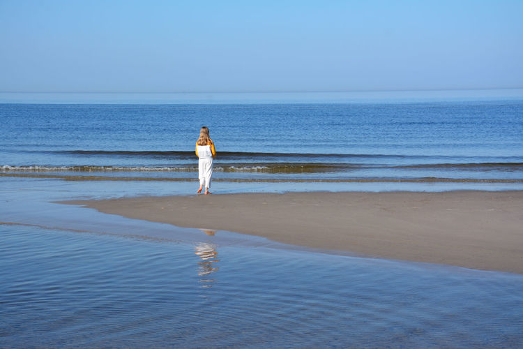 Rear view of girl walking on shore at beach against sky during sunny day
