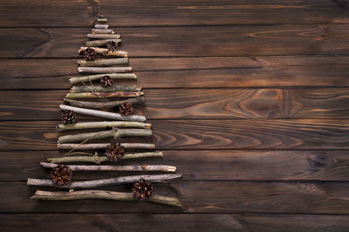 Christmas tree made of dry wooden branches with pine cones decoration on wooden table background. View from above. New Year and Christmas card background. Celebration Christmas Coniferous December Eve Happy Holiday Merry Christmas! New Year Pine Postcard Tree Winter Backgrounds Banner Branch Card Cone Decorative Gift Greetings Table Wallpaper Wood - Material Woods