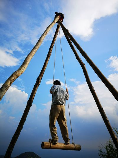 Low angle view of man sitting on rope against sky