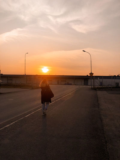Rear view of man walking on road at sunset
